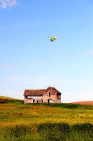 Crop Duster over Old House